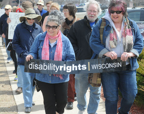 group of people for disability rights marching with sign that says disability rights wisconsin down side walk.