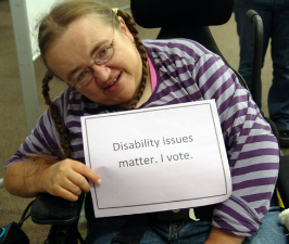woman with disability holding a sign that say Disability Issues matter. I vote.