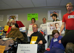 Individuals with disabilities speaking out against Medicaid cuts at public forum.