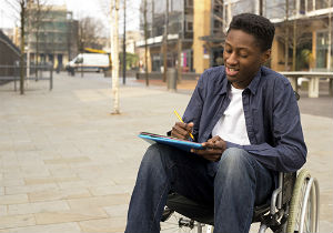 Young man in a wheelchair writing a letter outside.