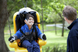 child with a disability on a swing having fun with parent