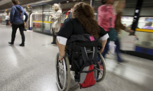 Woman in wheelchair catching the subway train.