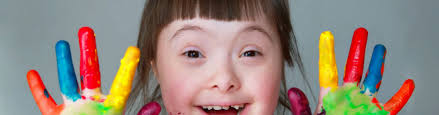girl with downs syndrome with painted fingers smiling