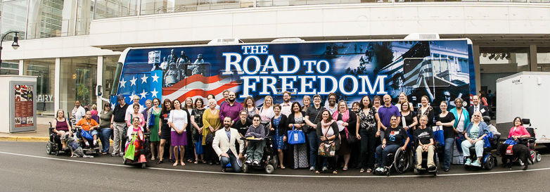 Disability rights wisconsin staff standing in front of the ADA road to freedom bus.