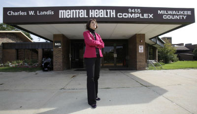 Barbara Beckert, Milwaukee office director, standing in front of Milwaukee county Mental Health Complex (MHC) with arms crossed.
