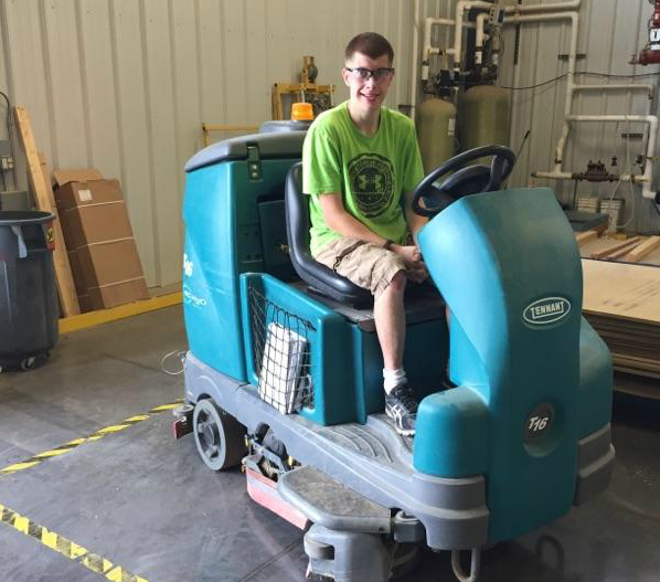Bryce driving a floor cleaner at his new job.