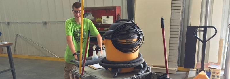 Client Bryce pushing his utility cart at his job with his safety glasses on smiling.