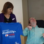 Barbara Beckert holding a Wisconsin Disability Vote Coalition t-shirt and Ramsey Lee