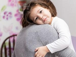 Girl hugging parent with sad eyes