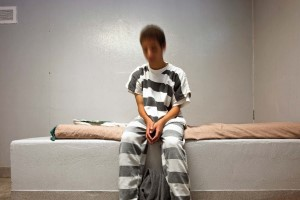 Boy in jail suit with blurred face sitting on jail bed