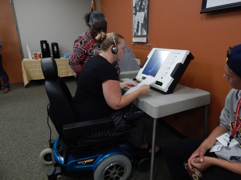Voter in a wheelchair using an accessible voting machine with others looking on
