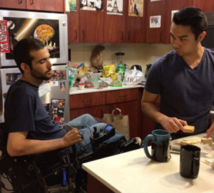 Man in wheelchair with his personal attendant making lunch in the kitchen.